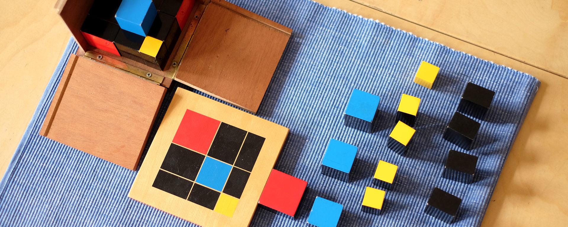 Hölzerne Montessorimaterialien für den Matheunterricht auf einem Teppich