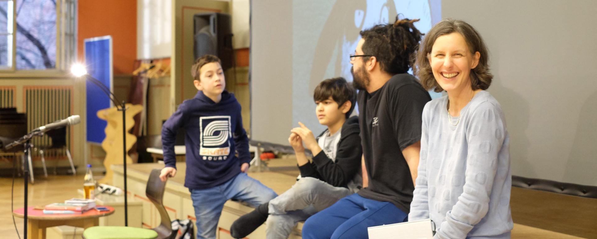 Die Vorsitzende des Fördervereins mit Autor und zwei Schülern bei einer Lesung in der Aula