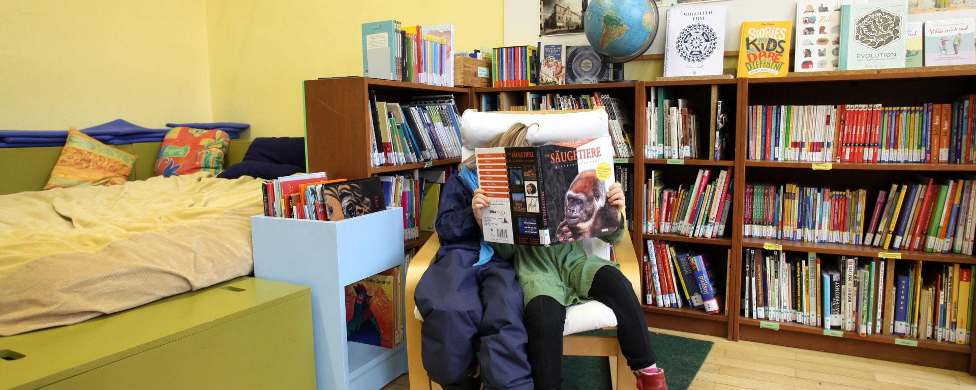 Zwei Schüler*innen teilen sich einen Stuhl beim Lesen in der Schulbibliothek
