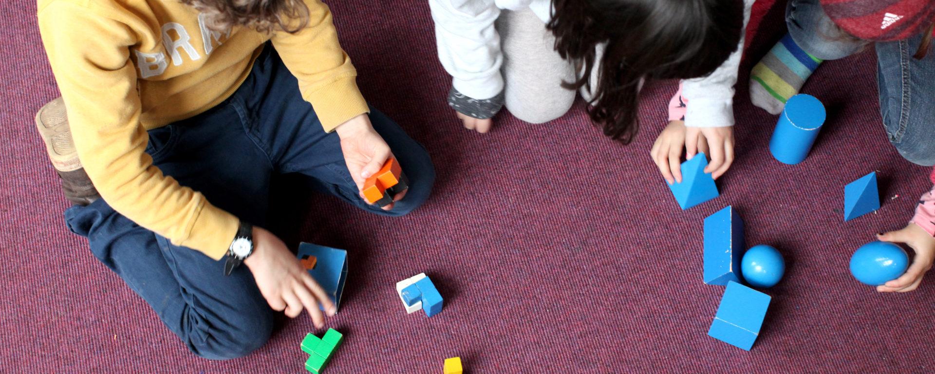 Schüler*innen lernen mit Montessorimaterialien geometrische Formen kennen