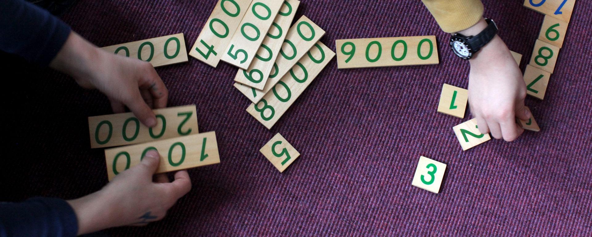 Montessorimaterialien für den Matheunterricht werden von zwei Kindern ausgelegt