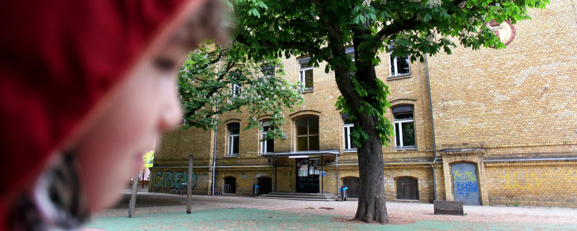 Schüler im Anschnitt vor dem gelben Haus der Schule