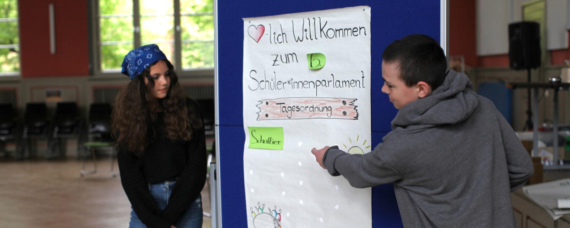Zwei Schülervertreter*innen sammeln Punkte für die Tagesordnung beim Schüler*innenparlament